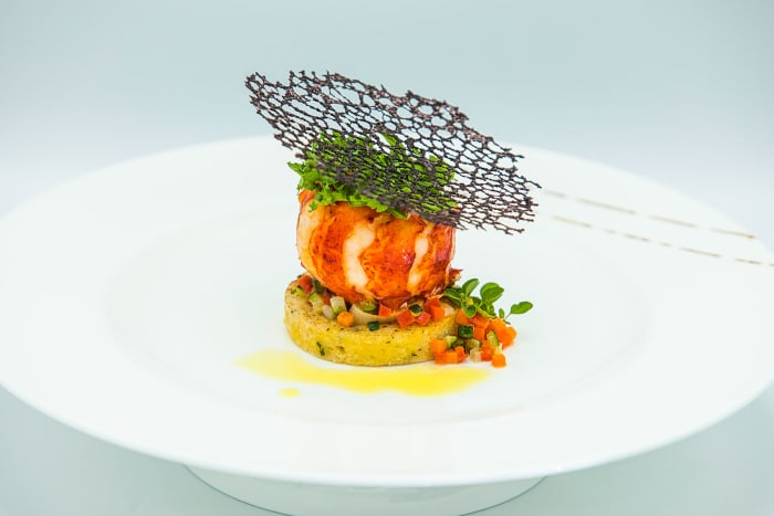 The chef's award-winning butter-poached lobster tail on a polenta round with brunoise, braised leeks and coral tuille.