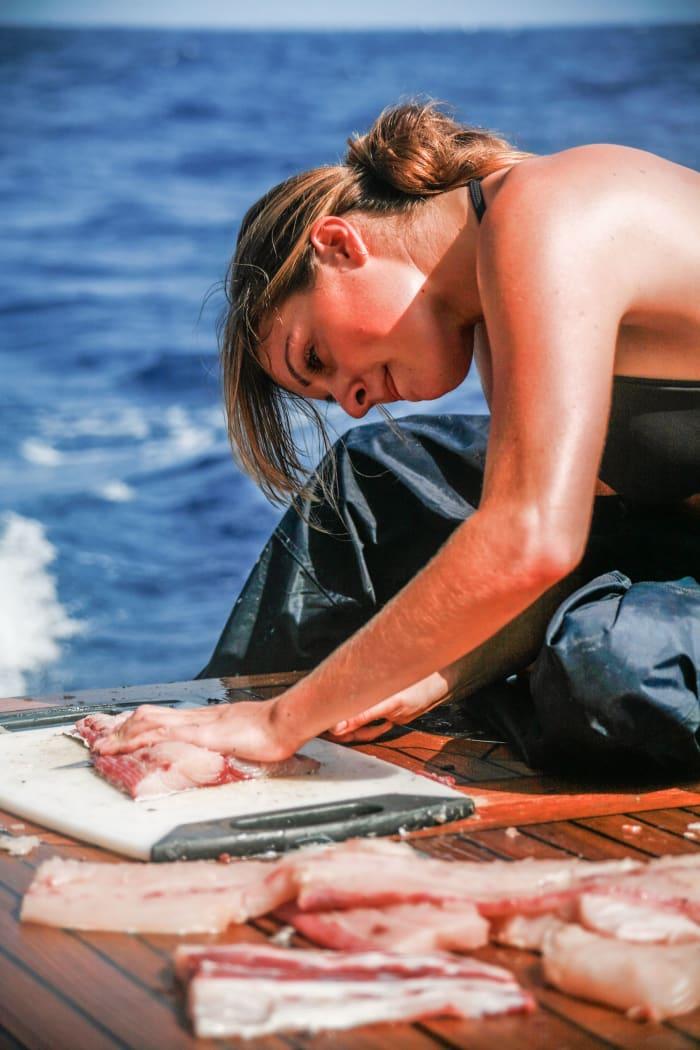 Elizabeth Lee fillets freshly caught mahi-mahi on deck during an Atlantic crossing.