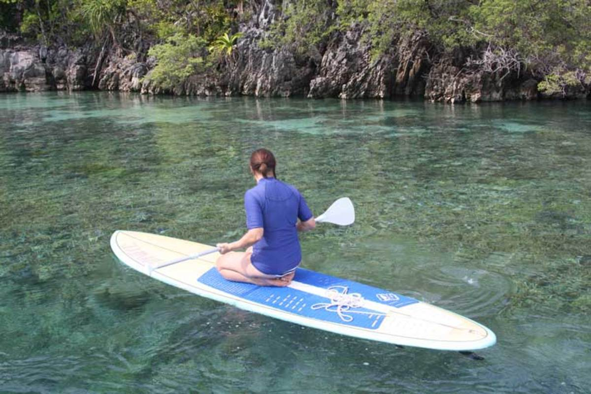 Paddle boarding over visible coral beds near the water's surface.