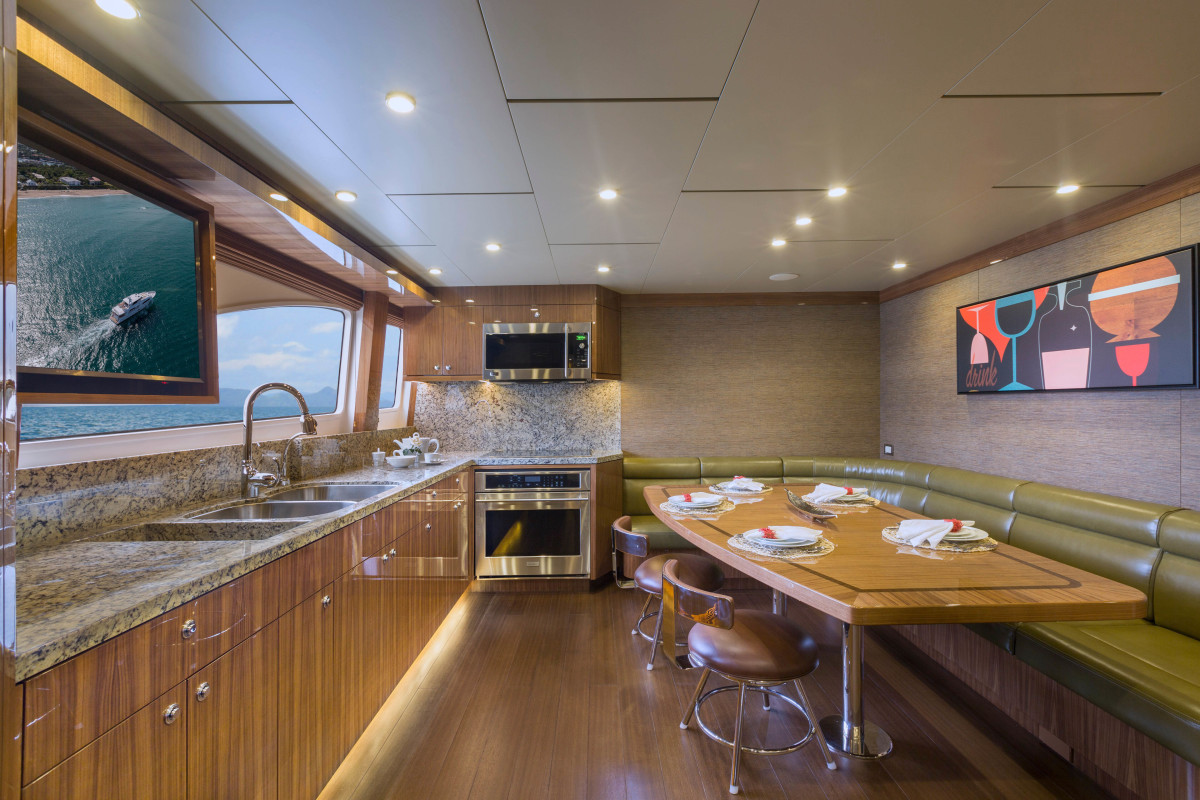 A 40-inch TV in the galley keeps guests entertained. Note the wide-open layout and large dining table to accommodate plenty of family enjoyment while cooking in the galley.