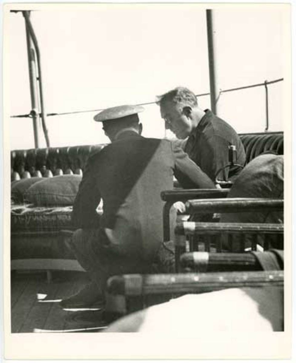 President Franklin Delano Roosevelt confers with a naval officer aboard the presidential yacht USS Potomac.