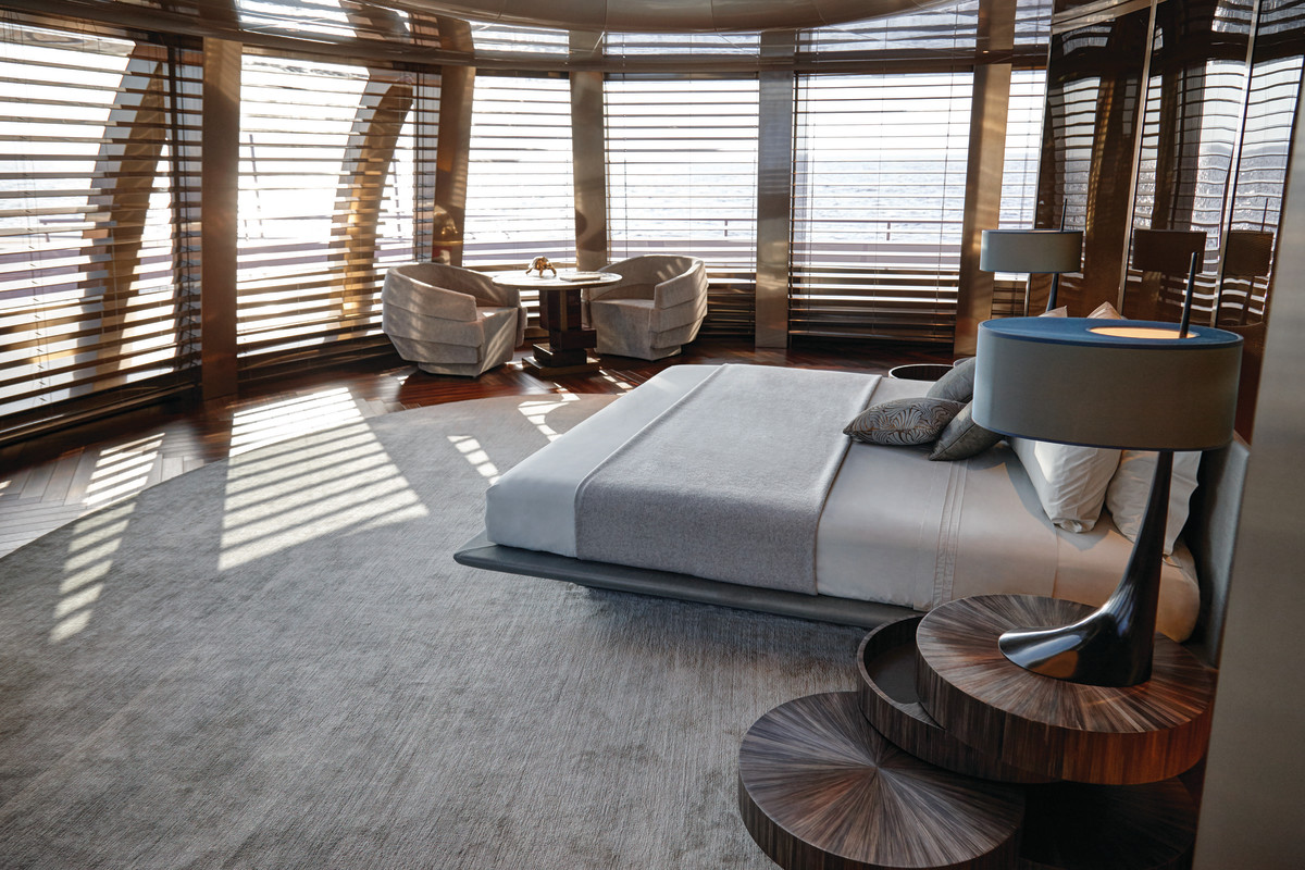 The forward-facing master stateroom has a panoramic view with outside access through pantograph doors. The master suite is an uncluttered space with onyx bathrooms and no doors, except at the entrance to the bedroom, which has a curved fireplace with electric candles for ambience.