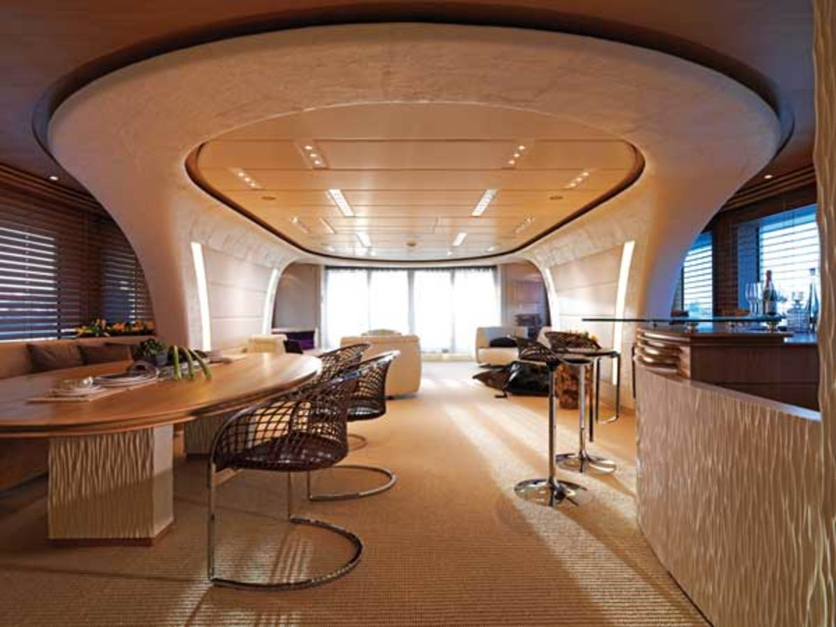 The open-plan main salon features curvilinear sculptural structures and furniture that is oval-shaped or rounded.