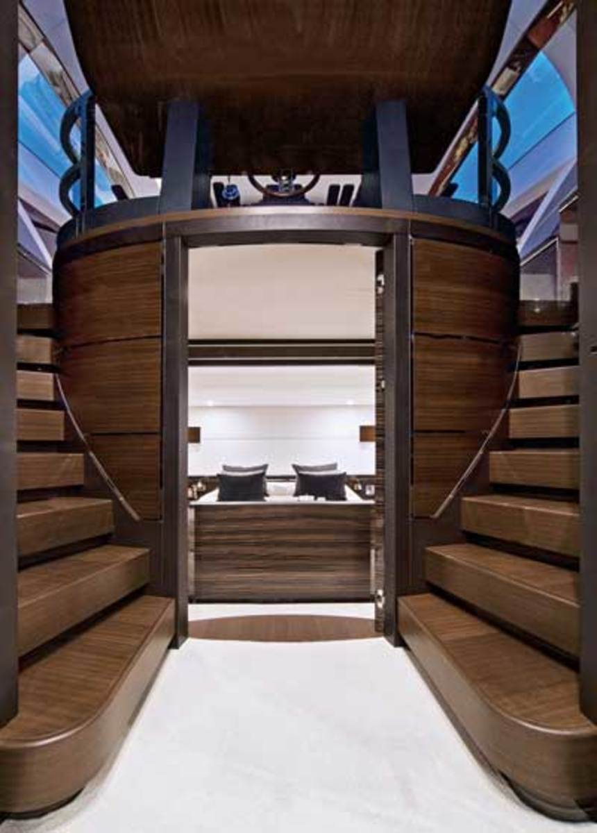 Leading down from deck level, mirrored stairways frame the striking helm pedestal above the master stateroom.