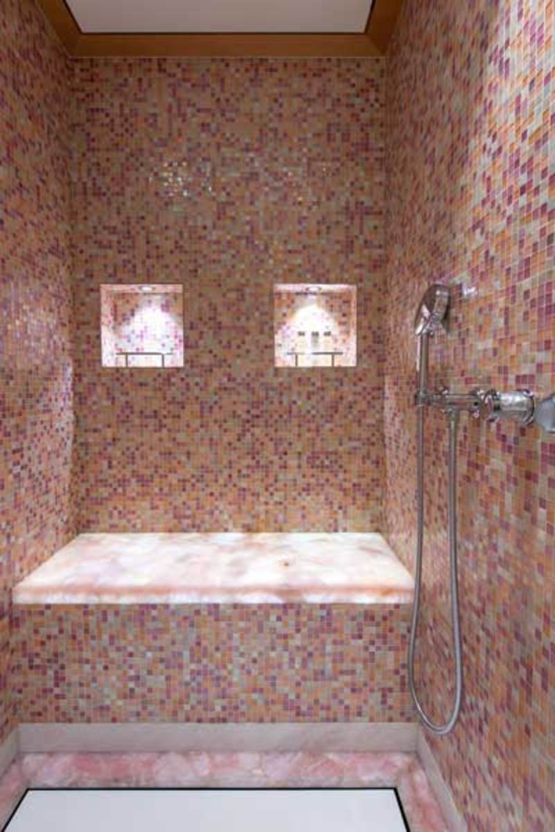 The owner's vast marble and mosaic-tiled shower stall.