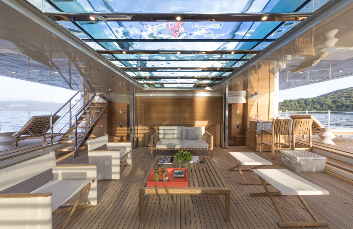 When the louvered transom door is raised and the tender is floated out, a teak-soled platform lowers from the ceiling to cover the bay, and two lateral shell doors in the hull can lower to extend the waterfront real estate. More natural light filters through the glass-bottomed swimming pool on the main deck above.