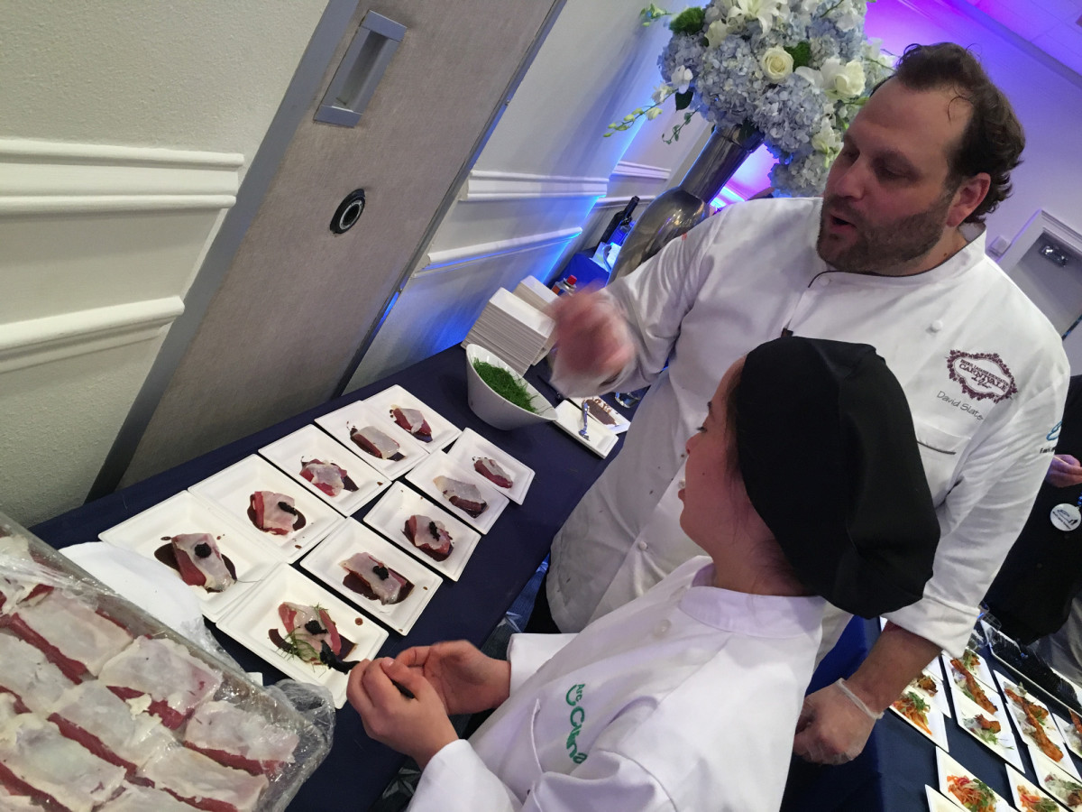 Chef David Slater and an Arc Broward culinary student prepare dishes for the Seafood Cookoff, a signature event at the Emeril Lagasse Foundation's second annual Line, Vine & Dine Fishing Tournament.