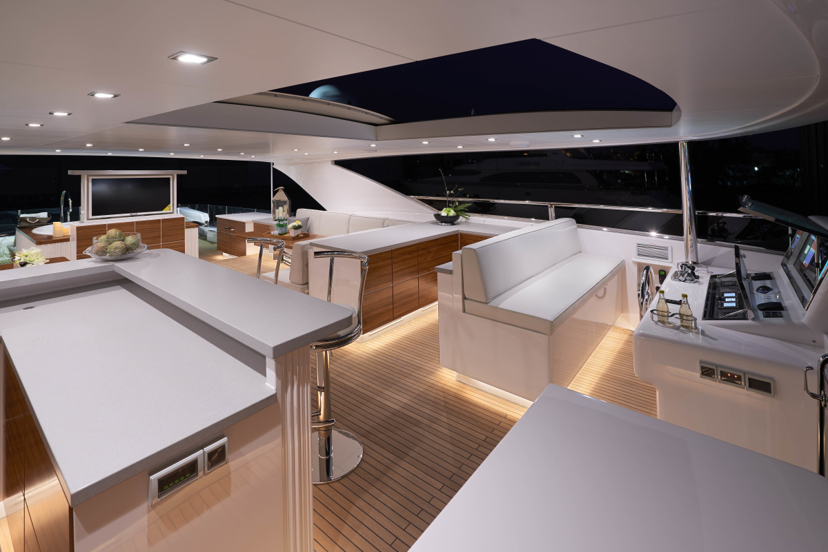 A hardtop with a built-in sunroof covers more than half of the flybridge, from the helm aft to the spa tub.
