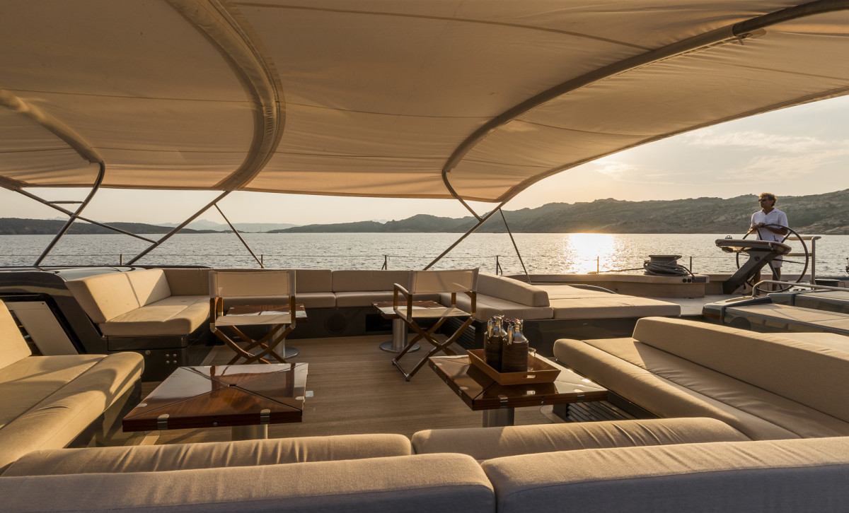 The expansive guest cockpit offers shaded, open-air relaxation with the bimini raised in cruiser mode.