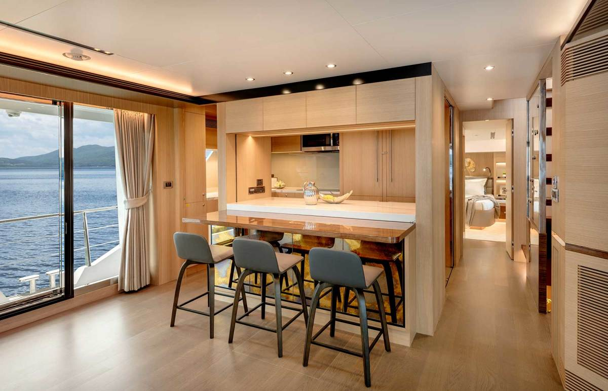 The foyer conceals a stacked washer-dryer behind artistic paneling, while the galley sports a bar that doubles as a buffet.