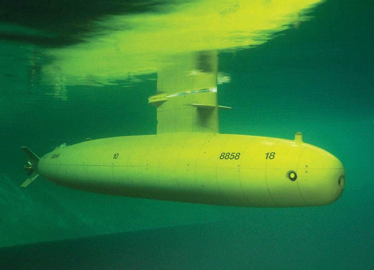 The test submarine operating semi-submerged in a model basin.