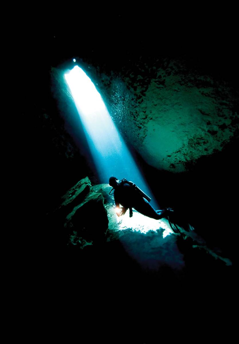 The owner explores a cenote, an underground freshwater cave, in Yucatán, Mexico.