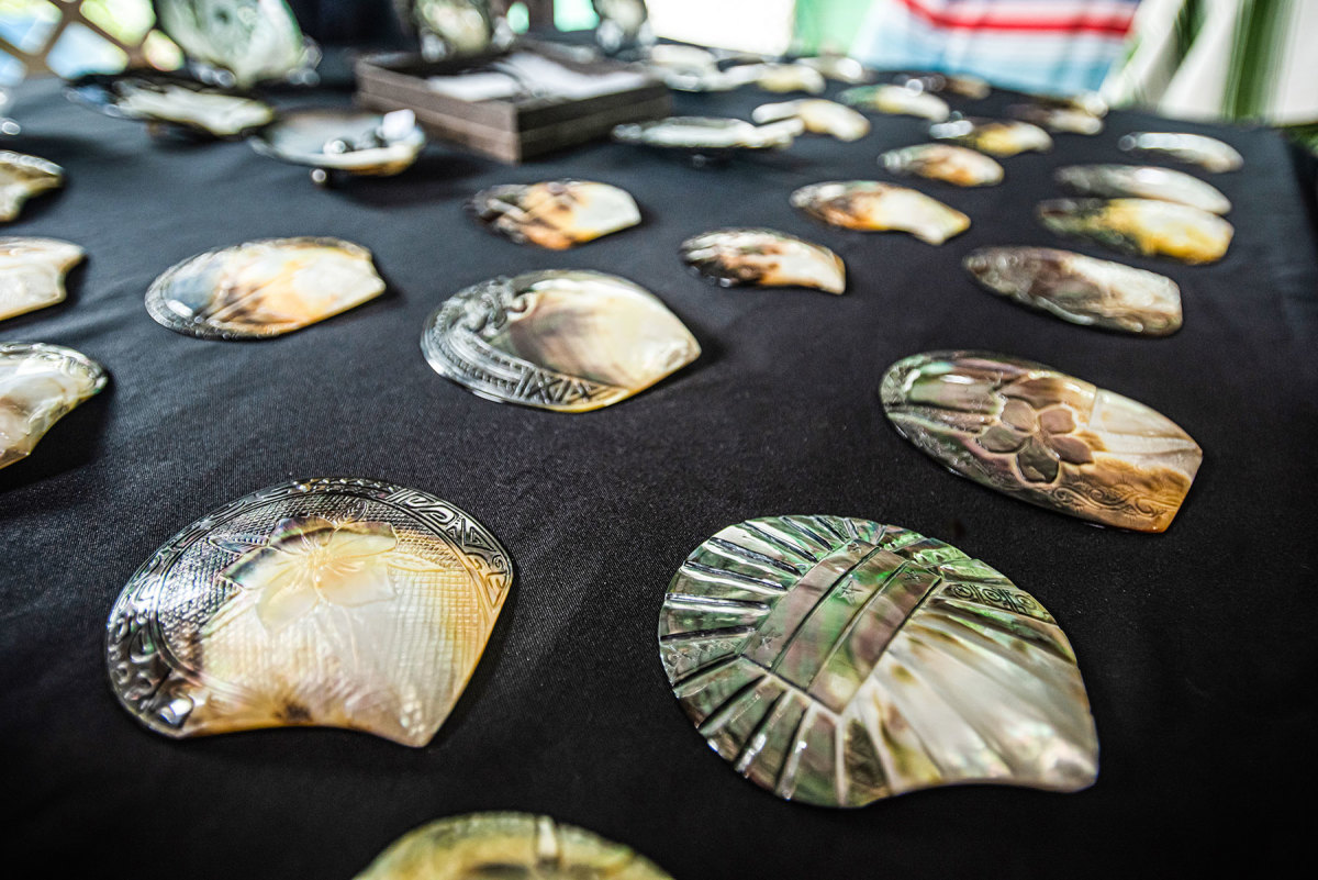 Local artists in Rikitea carve intricate designs into mother-of-pearl shells.
