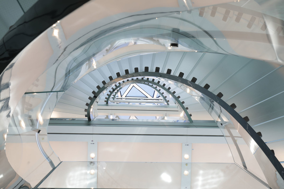 A glass staircase in the shape of an eye seems to float as you ascend from the lower deck upward toward the skylight.