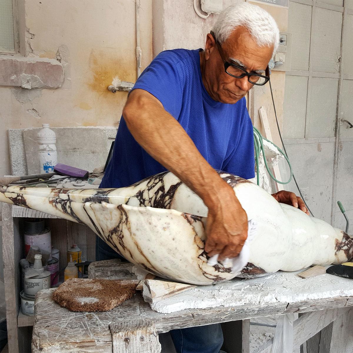 Roberto Quai hand-polishes a tibia shell of breccia violetta marble.