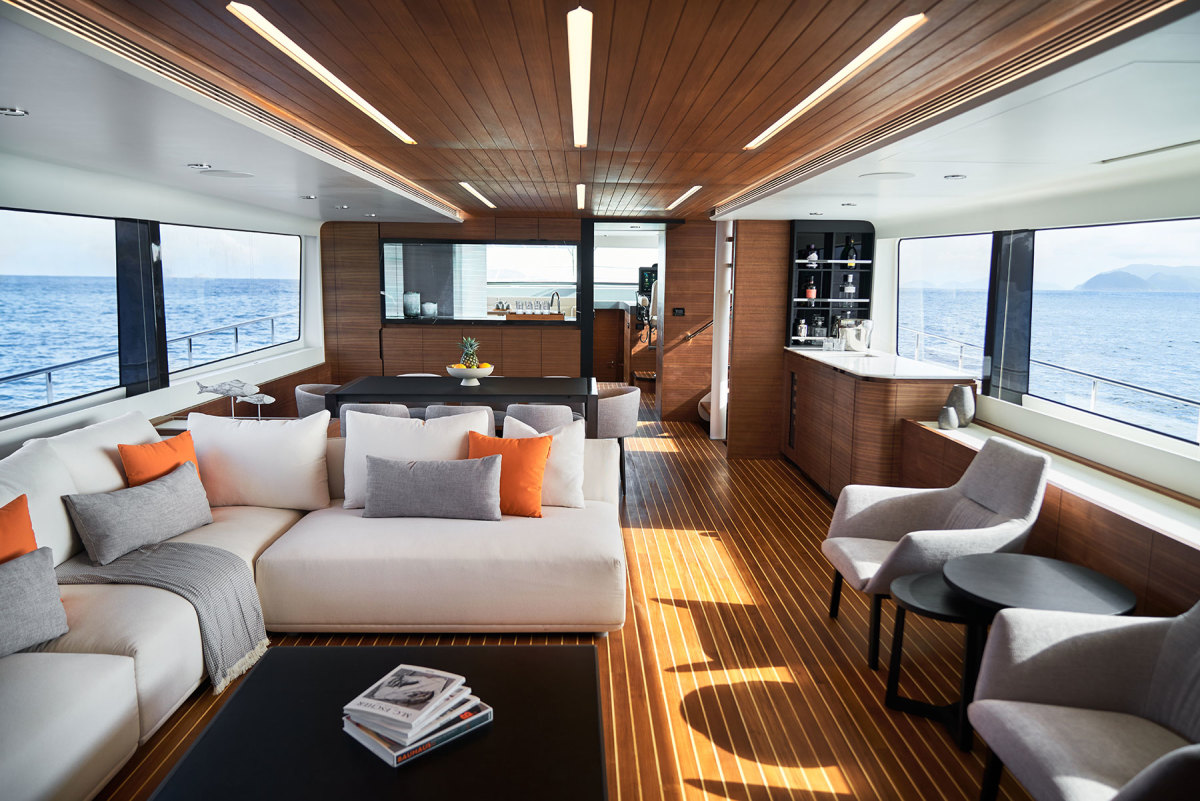 The main deck's open layout is complemented by large side windows spanning nearly the entire deck, and accented by  pillows upholstered in CL's signature orange.