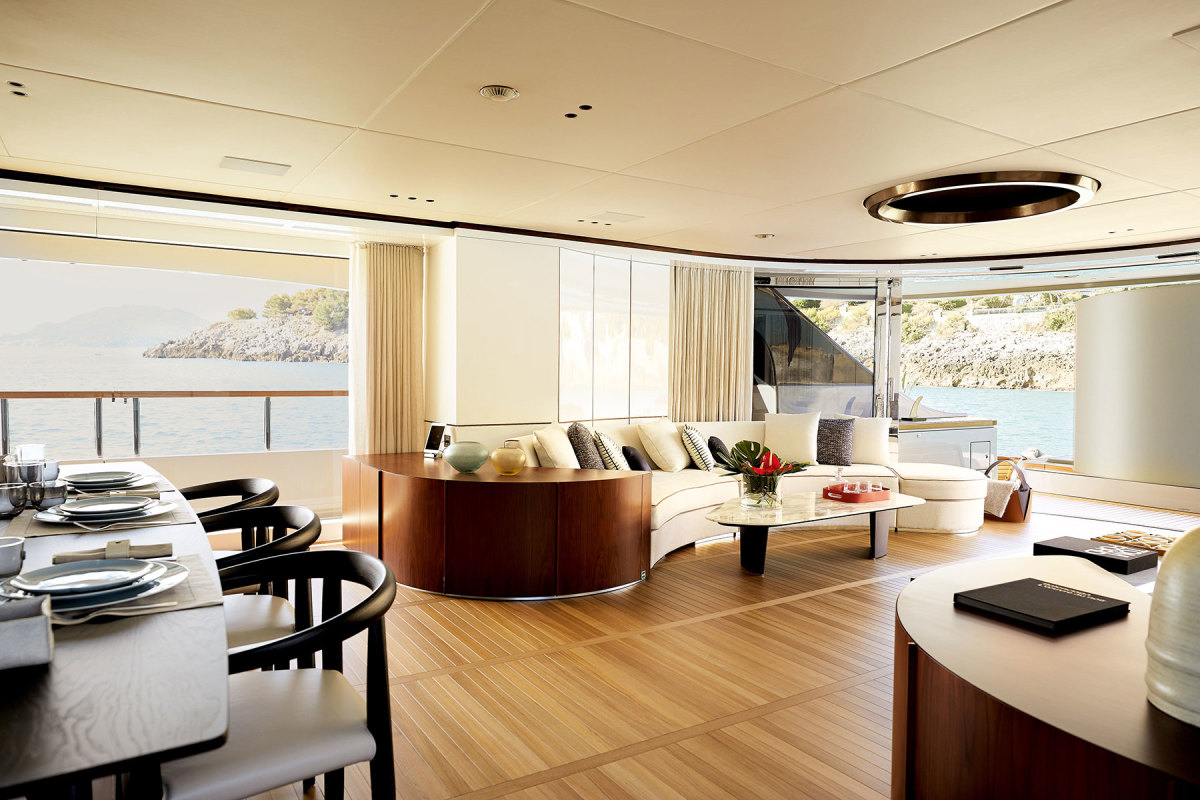 The main salon opens directly onto the aft deck through a grand semicircle of sliding glass.