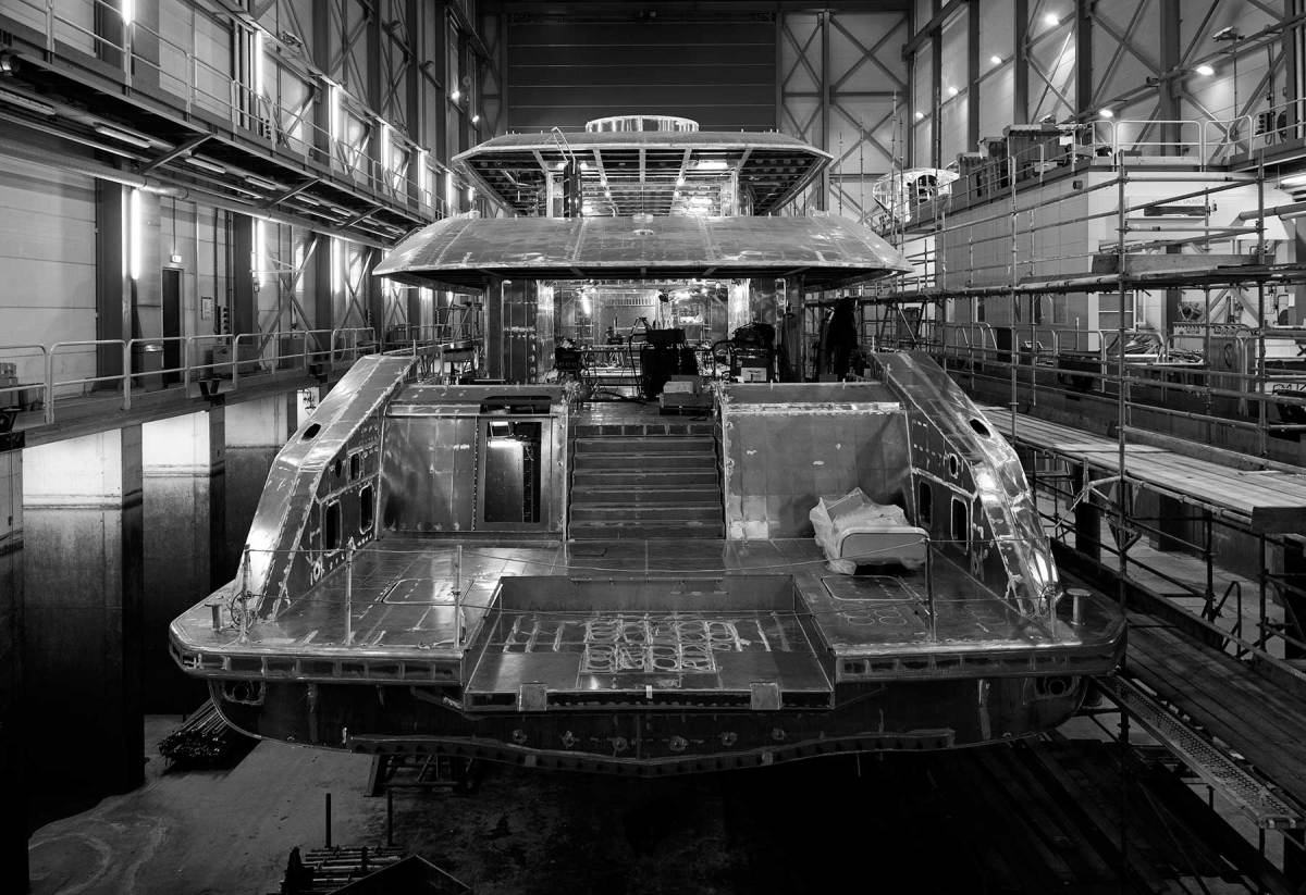 A gleaming, all-aluminum Heesen yacht is prepared for fitting out in the dry dock.