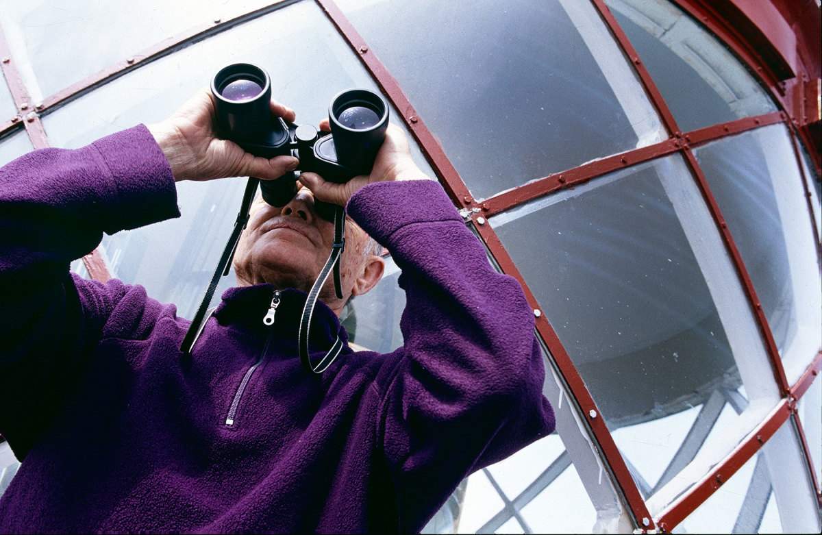 A volunteer scans the horizon from the gallery of the Obrestad lighthouse.