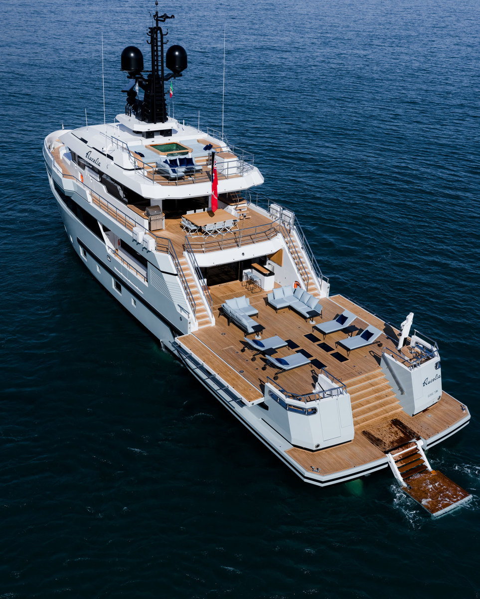 Aurelia in beach club mode with her tenders launched, crane retracted into the deck and side bulwarks deployed.
